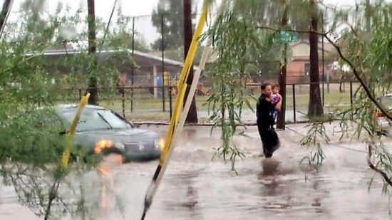 Tucson police officer carries a small child away from flooding. (Twitter Photo/@Tucson_Police)
