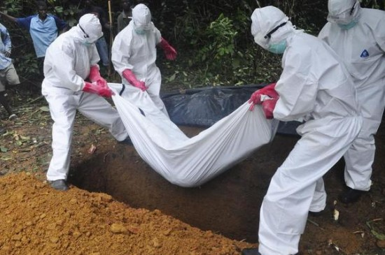 A burial team in protective gear bury the body of woman suspected to have died from the Ebola virus in Monrovia, Liberia. Saturday, Oct, 18, 2014. (Image source: AP/Abbas Dulleh)