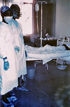 A 1976 photograph of two nurses standing in front of Mayinga N'Seka, a person with Ebola virus disease in the 1976 outbreak in Zaire. N'Seka died a few days later due to severe internal hemorrhaging.